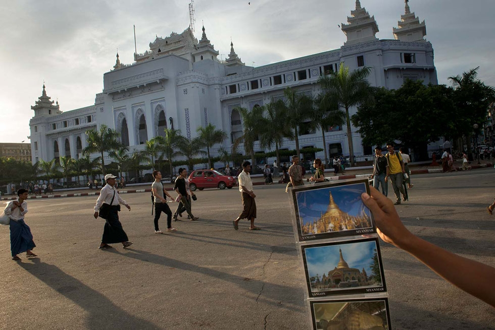 A boy hawks postcards of Myanmar's monuments to a visitor in front of Yangon city hall. (Gilles Sabrié)