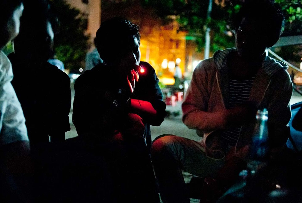 In a dimly lit street of Yangon, youth share a joint. The use of weed is very common among Burmese youth. (Gilles Sabrié)