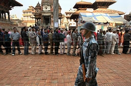 Kathmandu, April, 10, 2008 - As the country goes to the polls, Nepalese men queue to cast their ballots while a soldier patrols the streets. (PEDRO UGARTE/AFP/Getty Images)