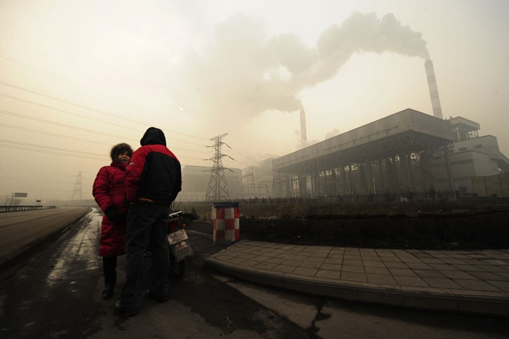 This photo taken on December 8, 2009 shows two people outside a coal-powered power plant on the outskirts of Linfen, China, regarded as one of the cities with the worst air pollution in the world. (Peter Parks/AFP/Getty Images)