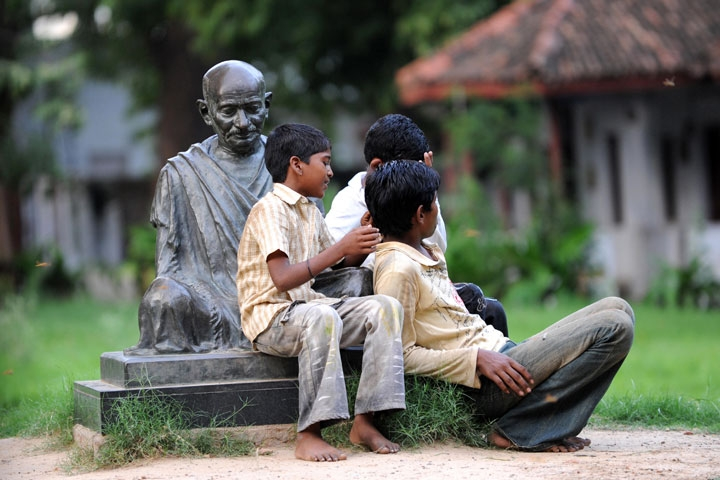 Indian boys sitting on the Mahatma Gandhi statue at the Gandhi Ashram in Ahmedabad in Aug. 2009. (Sam Panthaky/AFP/Getty Images)