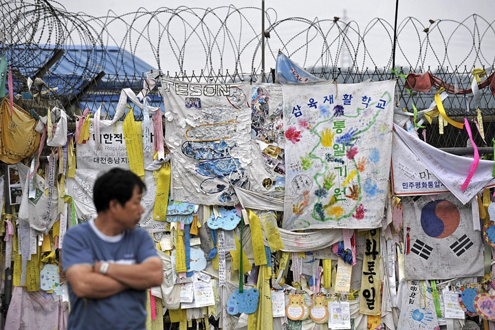 A man looks at reunification banners displayed on the fence of the Freedom Bridge, near the DMZ separating South and North Korea, in Paju on June 2, 2009.  (Philippe Lopez/AFP/Getty Images)