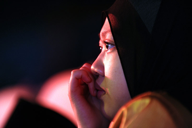 A young Malaysian woman watches contestants perform in Malaysia's reality TV competiton Young Imam in Kuala Lumpur on July 30, 2010. (Saeed Khan/AFP/Getty Images)