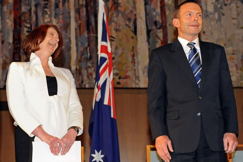 Australian Prime Minister Julia Gillard (L) laughs beside Federal opposition leader Tony Abbott (R) after she finally secured enough independents to form the new government at Parliament House in Canberra on September 7, 2010. (Torsten Blackwood/AFP/Getty Images)