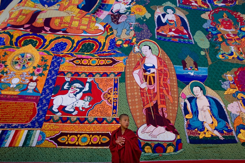 A Bhutanese monk stands in front of a large Thangkha painting at the Dratshang Kuenra Tashichho Dzong on November 6, 2008 in Thimphu, Bhutan. (Paula Bronstein/Getty Images)