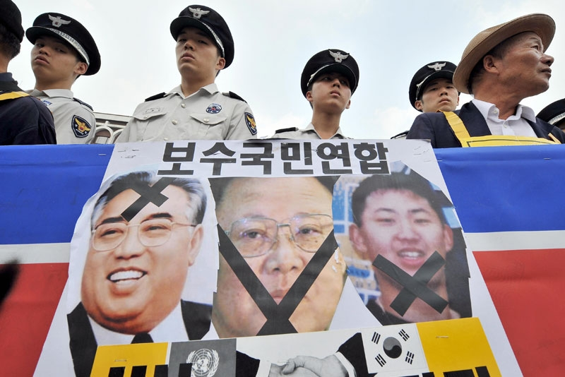 South Korean police watch a conservative activists standing behind a North Korean flag with pictures of the North's late president Kim Il-Sung (L), his son and current leader Kim Jong-Il (C) and grandson Kim Jong-Un (R), during an anti-Pyongyang rally in Seoul on July 8, 2009. (Jung Yeon-Je/AFP/Getty Images)