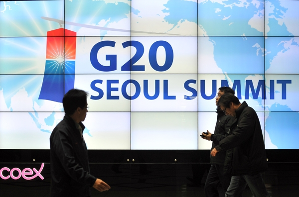 Visitors walk in front of a screen showing a sign for the upcoming G20 Summit at its venue in Seoul on November 4, 2010. (Jung Yeon-Je/AFP/Getty Images)