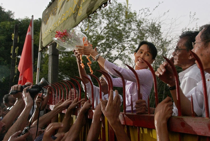 Burma/Myanmar's detained opposition leader Aung San Suu Kyi holds a bouquet of flowers as she appears at the gate of her house after her release in Yangon (Rangoon) on November 13, 2010. The lakeside home had been her prison for most of the past two decades. (Soe Than Win/AFP/Getty Images)
