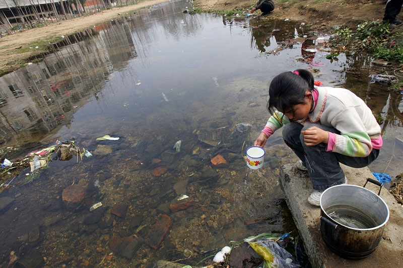 A girl collects water from a ditch in Hubei Province, China, in Mar. 2008. In China, an estimated 300 million rural residents still have low access to safe drinking water, and 400 cities face water shortages. (China Photos/Getty Images)