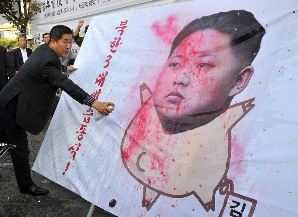 A South Korean activist paints on a caricature of Kim Jong Un, the youngest son and heir-apparent of North Korean leader Kim Jong Il, during a rally denouncing the communist country's third-generation dynastic succession in Seoul on October 14, 2010. (Jung Yeon-Je/AFP/Getty Images)