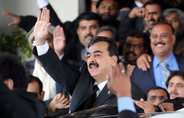 Pakistani Prime Minister Yousuf Raza Gilani (C) surrounded by security personnel and lawyers acknowledges the crowd as he leaves the Supreme Court after adjourning the contempt hearing in Islamabad on Jan. 19, 2012. (Aamir Qureshi/AFP/Getty Images)