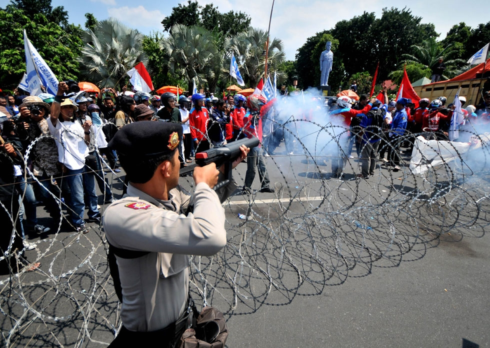 An Indonesian policeman shoots tear gas towards protesters during a protest against the government's plan to hike prices of fuel in Surabaya on March 29, 2012. (STR/AFP/Getty Images)