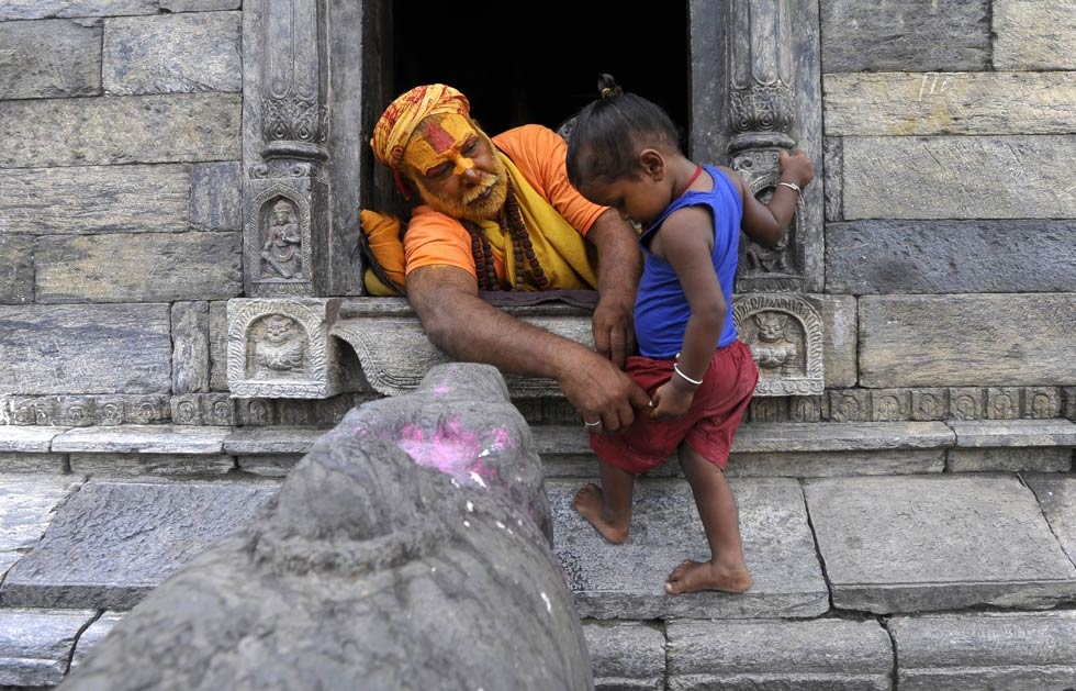A Hindu sadhu, or holy man, plays with a small child at the Pashupatinath Temple in Kathmandu on July 31, 2013. (Prakash Mathema/AFP/Getty Images)