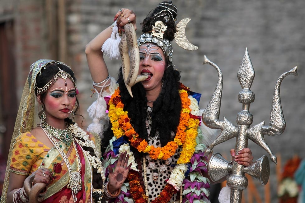 Indian Hindu devotees dressed as Hindu god Lord Shiva (R), seen holding a snake to his mouth, and Mata Parvati (L) participate in a procession on the eve of the Shivaratri festival in Jammu, India on February 26, 2014. (Strdel/AFP/Getty Images)