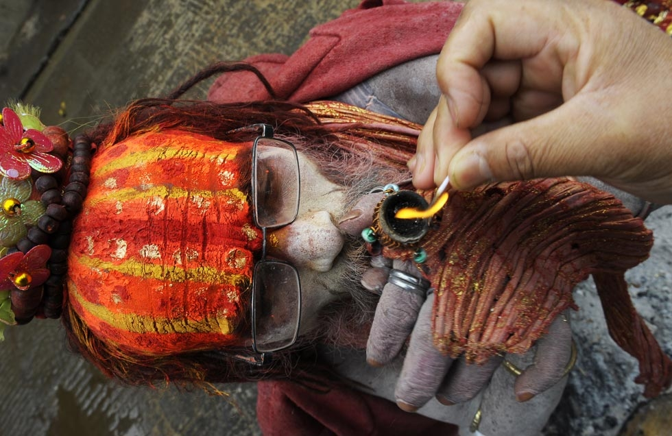 A Sadhu gets some help lighting a clay pipe as a holy offering for Lord Shiva during the Maha Shivaratri in Kathmandu, Nepal on February 27, 2014. (Prakash Mathema/AFP/Getty Images)