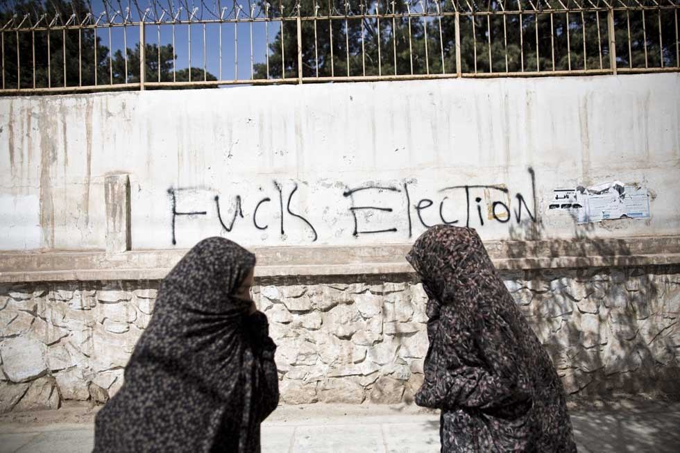 Afghans walk past graffiti against the upcoming presidential election in Herat on March 31, 2014. (Behrouz Mehri/AFP/Getty Images)