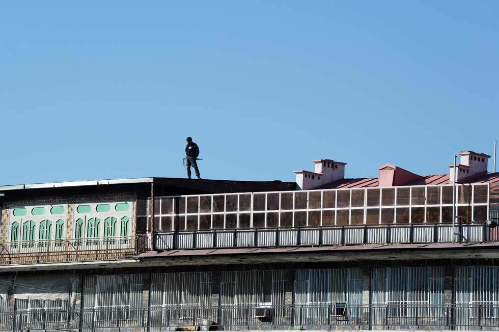 Police keep watch on the roof of a nearby building adjacent to the Afghan Ministry of Interior after a suicide bomber blew himself up at a nearby entrance to the interior ministry in central Kabul on April 2, 2014. (Shah Marai/AFP/Getty Images)