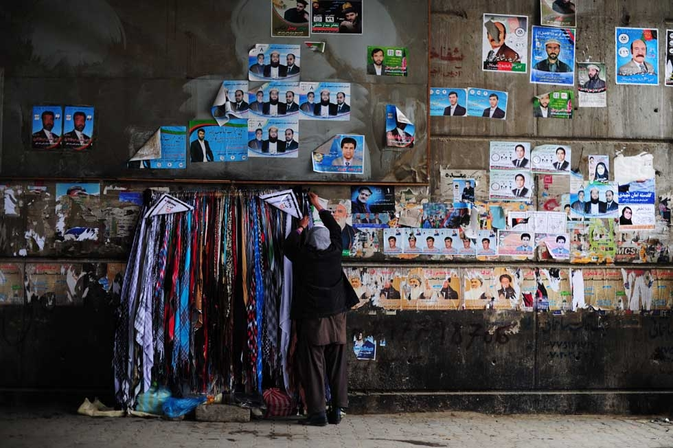 An Afghan roadside vendor hangs scarves next to political leaflets on a wall in Kabul on April 4, 2014. Some 12 million Afghans will go to the polls on April 5 to elect a new President. (Roberto Schmidt/AFP/Getty Images)