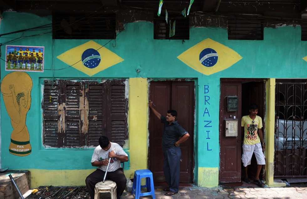 An Indian mechanic (L) sits in front of a house painted with the Brazilian national flag and and an image of the FIFA World Cup in Kolkata on June 15, 2014. (Dibyangshu Sarkar/AFP/Getty Images)