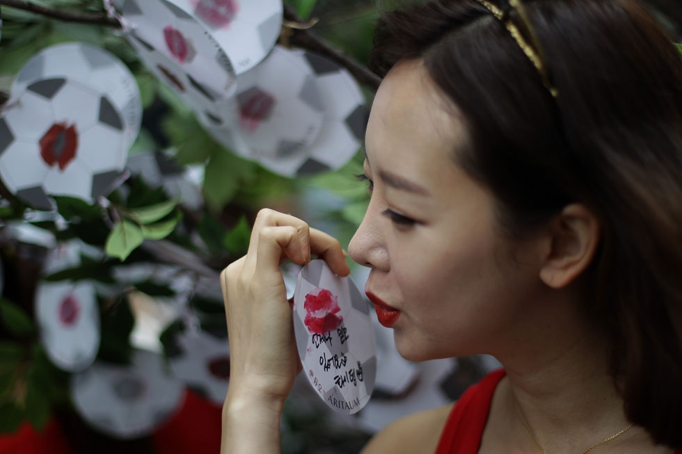A woman kisses a paper soccer ball during an event wishing for the South Korean team's success in the 2014 World Cup on June 12, 2014 in Seoul. (Chung Sung-Jun/Getty Images)