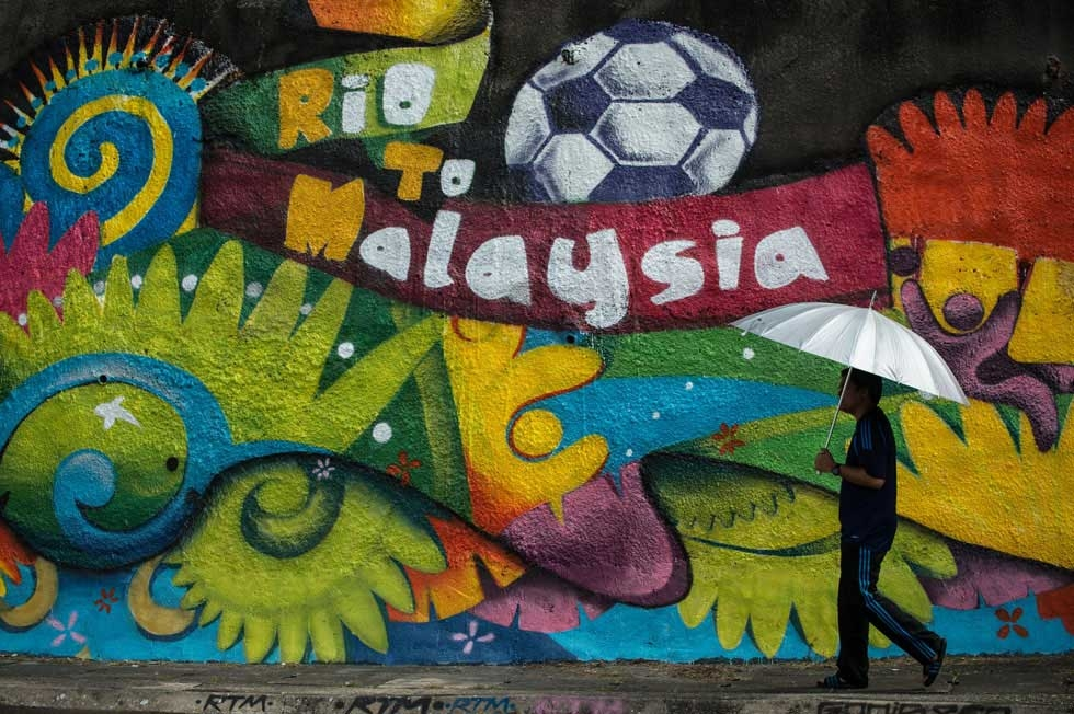 A man walks past graffiti celebrating the 2014 World Cup in Kuala Lumpur on June 12, 2014. (Mohd Rasfan/AFP/Getty Images)
