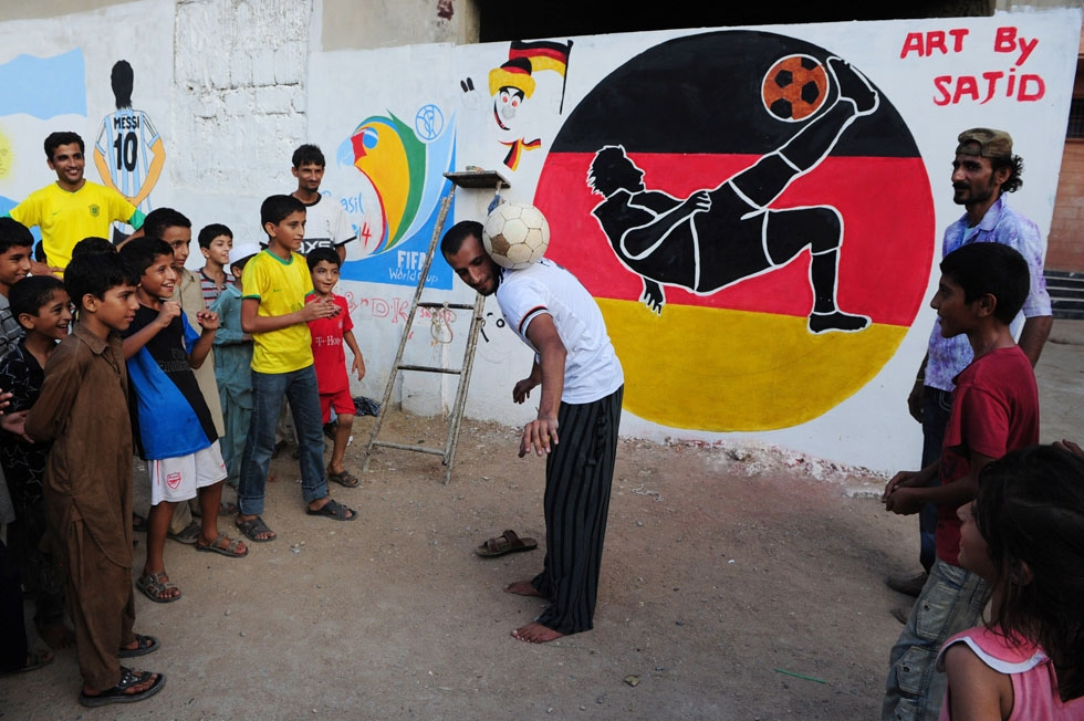 A Pakistani fan demonstrates his skills in front of a mural celebrating the World Cup painted on the wall of a house in Karachi on June 12, 2014. (Asif Hassan/AFP/Getty Images)