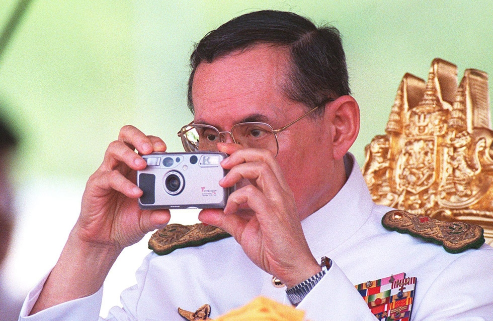 Thai King Bhumibol Adulyadej takes pictures during the royal ploughing ceremony in Bangkok. (Pornchai Kittiwongsakul/Getty Images)