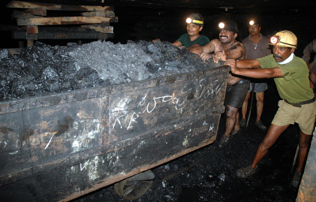 Indian coal miners push a trolley laden with coal inside an underground tunnel of a mine at Godavarikhani, July 27, 2007. (NOAH SEELAM/AFP/Getty Images)