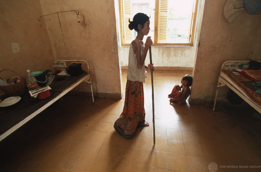 A woman suffering from HIV/AIDS uses a stick to walk back to her bed in hospital. Cambodia. (© Masaru Goto / World Bank)