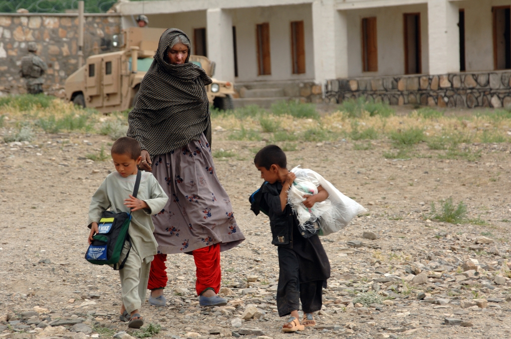 An Afghan woman walks home with her children carrying humanitarian goods after being seen by doctors with the Bagram Provincial Reconstruction Team during a medical civic action program in the district of Tagab in the Kapisa province of Afghanistan April 30, 2007. (Department of Defense)