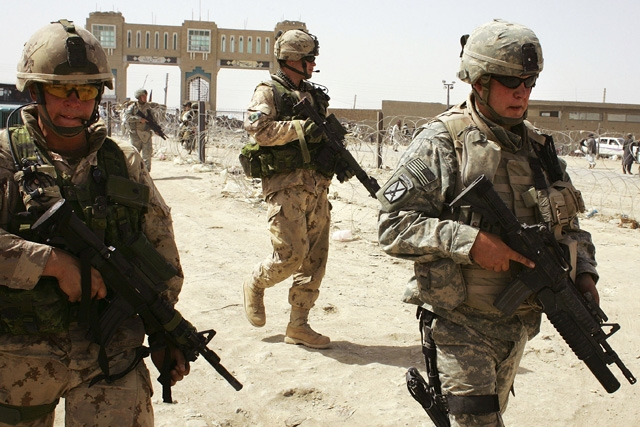 American, (R), and Canadian soldiers walk near the Afghan-Pakistan border crossing in support of Operation Mountain Thrust on June 19, 2006 at Spin Boldak, Afghanistan. (Photo by John Moore/Getty Images)
