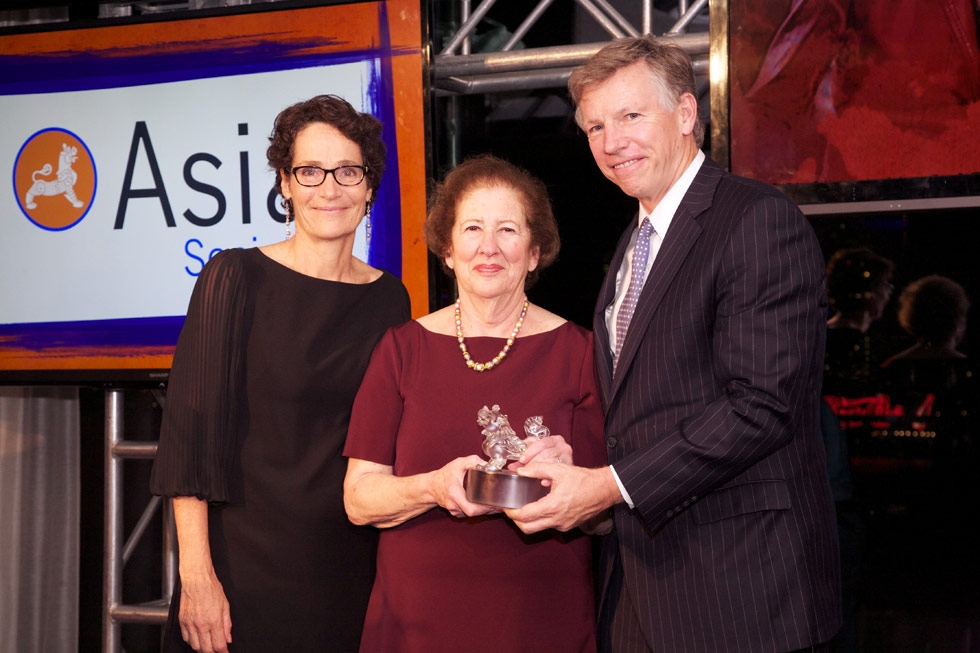 Betsy Cohen, center, presents an Asia Game Changer Award to Carlyle Singer and Bob Niehaus, accepting on behalf of Acumen's Jacqueline Novogratz. (Ann Billingsley/Asia Society)