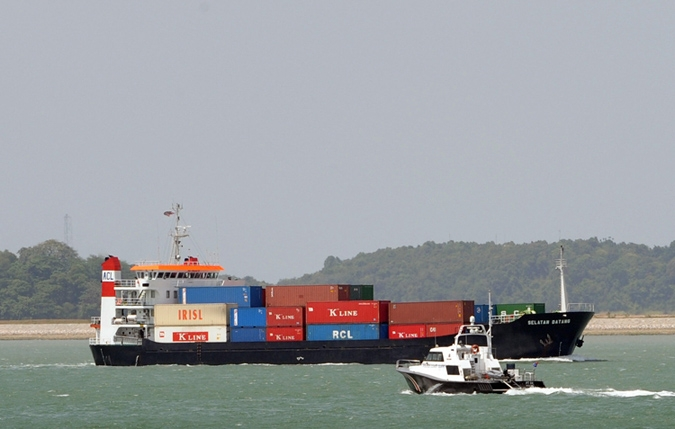 A vessel loaded with containers sails past a maritime coast guard on patrol along the Singapore Straits on February 20, 2008. (ROSLAN RAHMAN/AFP/Getty Images)
