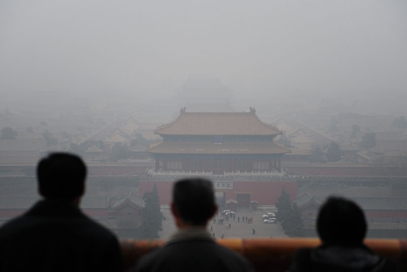Tourists take in the view of the Forbidden City from atop Coal Hill in Jingshan Park, north of the former imperial palace on a smoggy day in Beijing on December 10, 2009. (Frederic J. Brown/AFP/Getty Images)
