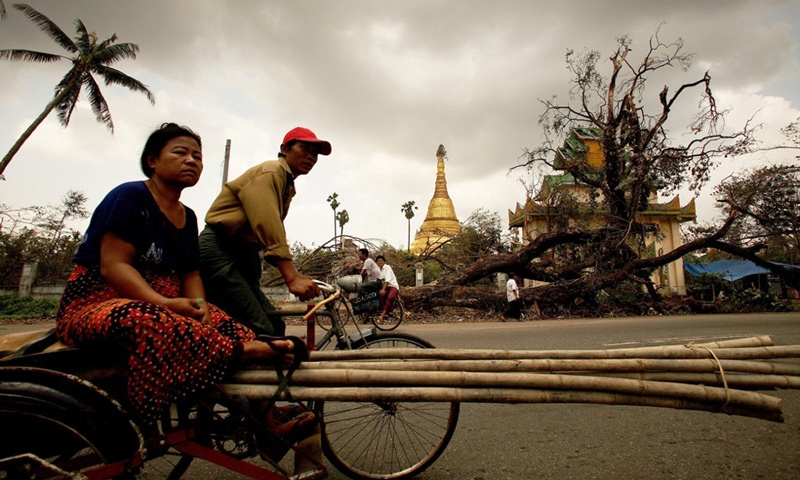 People ride a bike past an uprooted tree on May 8, 2008 in downtown Yangon. (Chumsak Kanoknan/Getty Images)