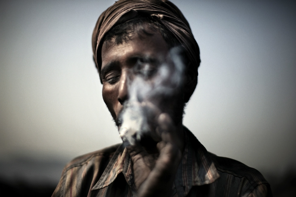 A miner smokes a cigarette during a rare break. (Erik Messori)