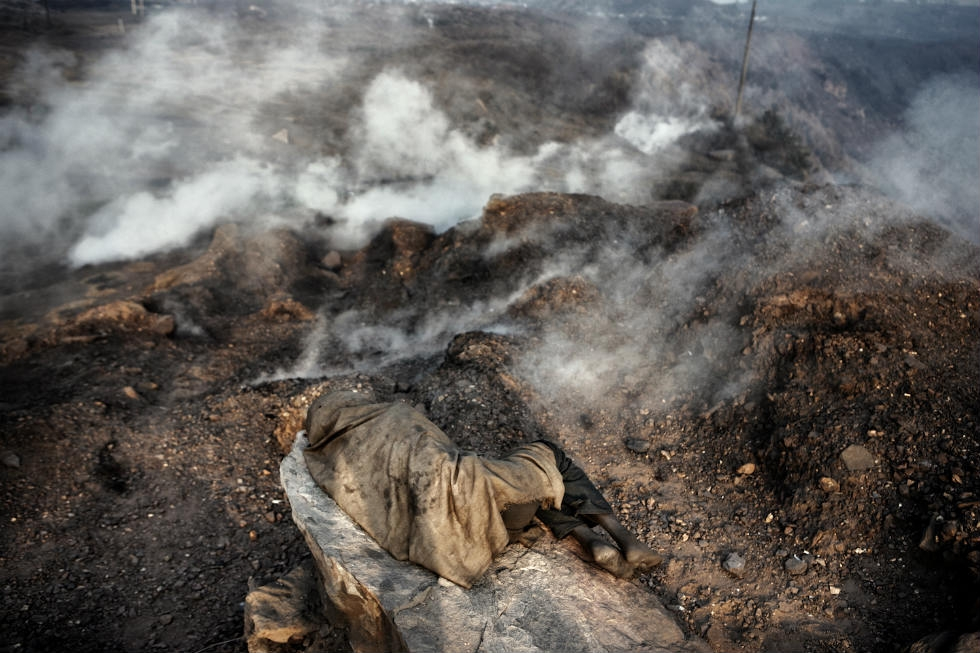An illegal miner rests and breaths carbon monoxide coming from underground burning coal. (Erik Messori)