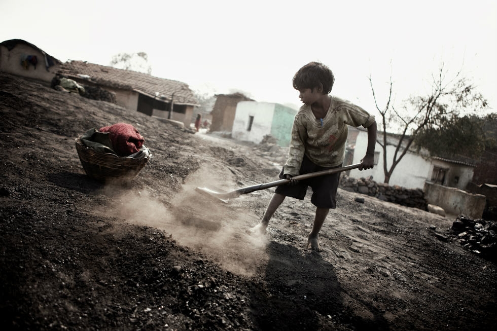 A child collects small fragments of coal. (Erik Messori)
