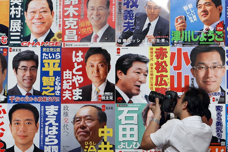 A journalist photographs Democratic Party of Japan campaign posters outside the Laforet Museum Roppongi in Tokyo, August 30, 2009. (Junko Kimura/Getty Images)