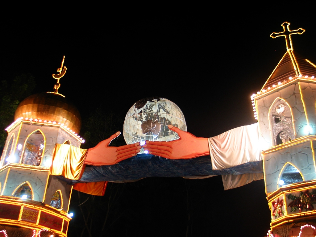 This is a Christmas structure in Naawan, a lively town in Misamis Oriental in the Philippines. it depicts a mosque (crescent) and a church (cross), with two hands reaching out to each other and holding the whole world. (Mercado/Flickr)