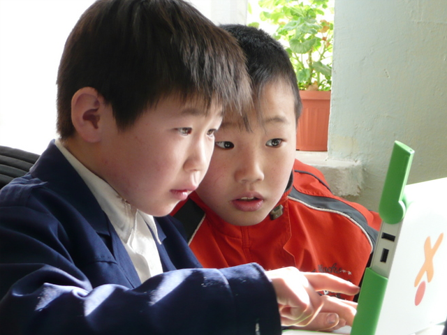 Students in Ulaanbaatar checking collaborating on an XO laptop. Photo: one laptop per child/flickr.com.