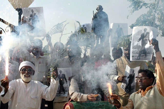 Indian tribal organisation activists from Jarkhand state light fireworks and hold up portraits of US president-elect Barack Obama as they celebrate in front of a statue of Mahatma Gandhi in Ranchi on November 5, 2008. (STR/AFP/Getty Images)