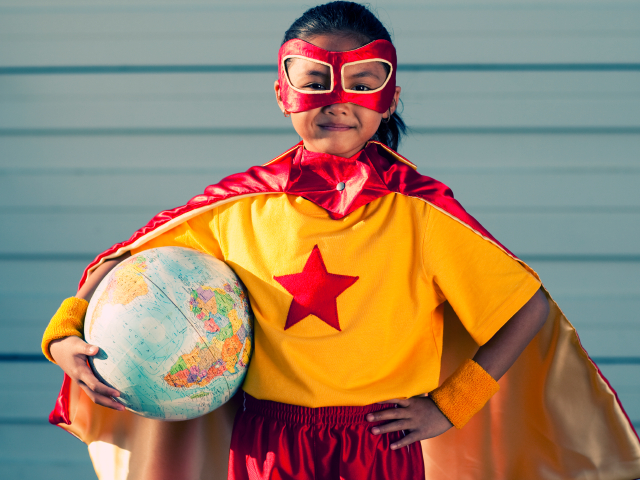 Girl dressed as superhero holding globe. (RichVintage/iStockPhotos)