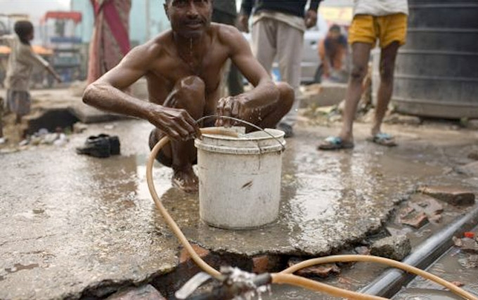 Local Indian residents in a west New Delhi slum use  a broken water pipe to bathe. In a city of 16 million people, one-quarter of New Delhi residents have no access to piped water. (Robert Nickelsberg/Getty Images)