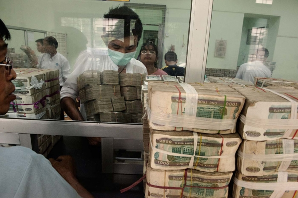 At a bank in downtown Yangon, gold and gem traders bring stacks of kyat (the local currency) to be exchanged for dollars. (Gilles Sabrié)