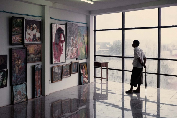 In an art gallery a visitor stares at a portrait of Aung San Suu Kyi. (Gilles Sabrié)