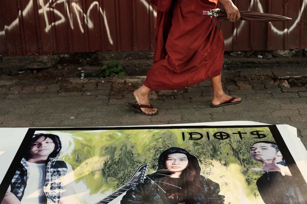 "A monk passes by a promotional poster for the local rock band ""Idiots."" (Gilles Sabrié)"