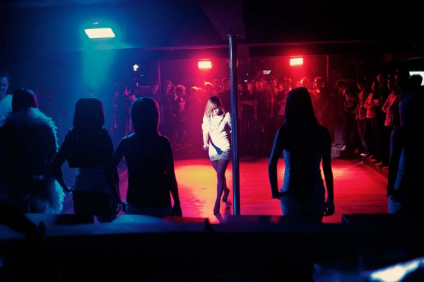 "In a club in Yangoon ""dancing girls"" walk in front of an all-male audience. Clubs hire ""dancing girls"" to entertain patrons. (Gilles Sabrié)"