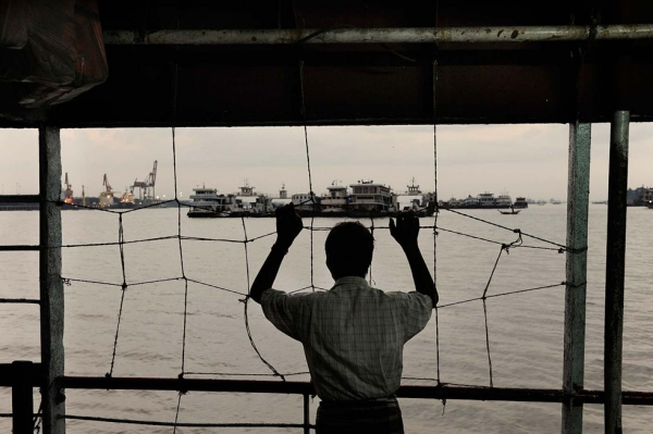 A man stares at Yangon harbor from a ferry. In spite of the reforms, Myanmar's economy is still in a dire situation. (Gilles Sabrié)