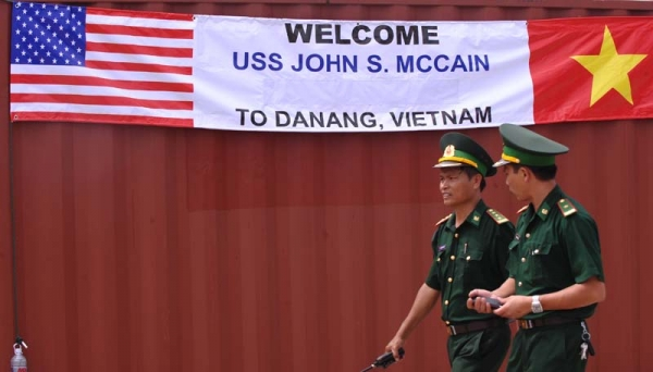 Two Vietnamese border-guard officers walk past a banner welcoming the port call by the US destroyer USS John S. McCain at Tien Sa port in the central costal city of Danang on August 10, 2010. (Hoang Dinh Nam/AFP/Getty Images)